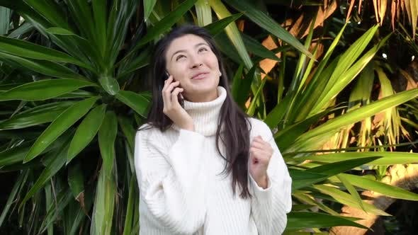 Young Asian Woman Use the Phone with Earphones While Walking