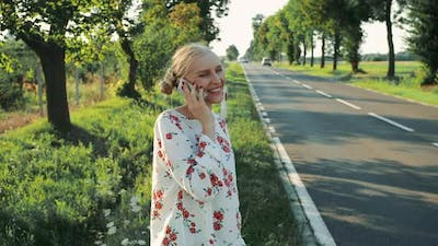 Young Lady Speaking on Phone While Hitchhiking