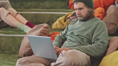 Hipster Working on Laptop in Lounge Area of Coworking Space
