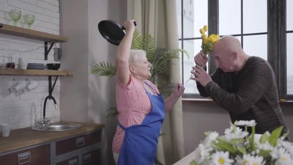 Thumbnail for Senior Caucasian Blond Woman Trying To Beat Her Husband with Frying Pan. Mature Baldheaded Man
