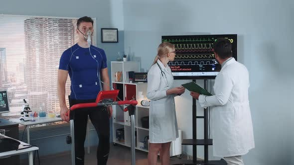 Thumbnail for Multiracial Scientists Examining the Athlete's Medical Records While He Stress Testing in Lab