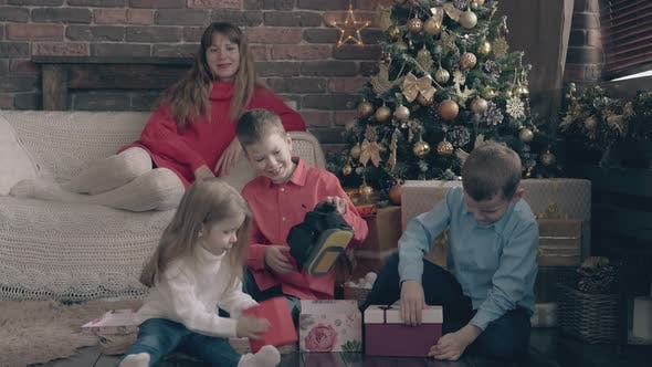 Thumbnail for Small Children Open Christmas Present Boxes Woman Watches