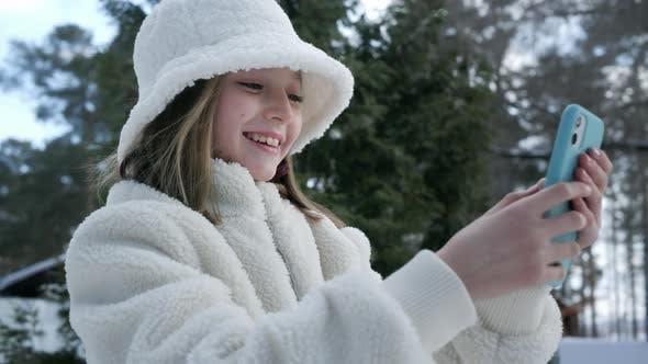 Junge Frau in weißem Hut und Pelzmantel mit Handy in der Winterstraße