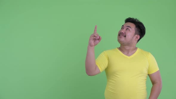 Thumbnail for Happy Young Overweight Asian Man Talking While Pointing Up