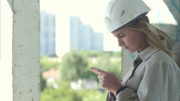 Thumbnail for Female Construction Engineer Holding Smartphone Standing in Construction Site