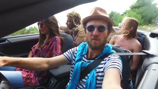Thumbnail for Bearded hipster man with a hat driving his friends in convertible