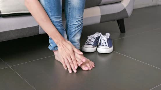 Thumbnail for Woman feeling itchy on feet at home