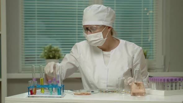 Thumbnail for Medical Doctor Woman In Mask And Glasses Uniform In Laboratory With Equipment