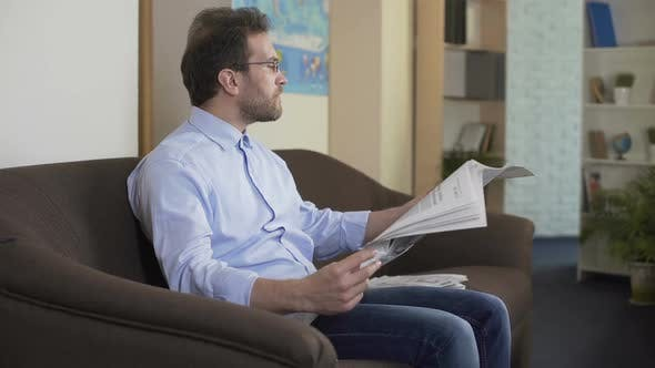 Thumbnail for Morning Ritual, Relaxed Man Sitting on Couch and Reading Newspaper at Home