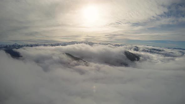 Thumbnail for High Aerial Above Epic Lowland Clouds In Snow Covered Mountain Valley