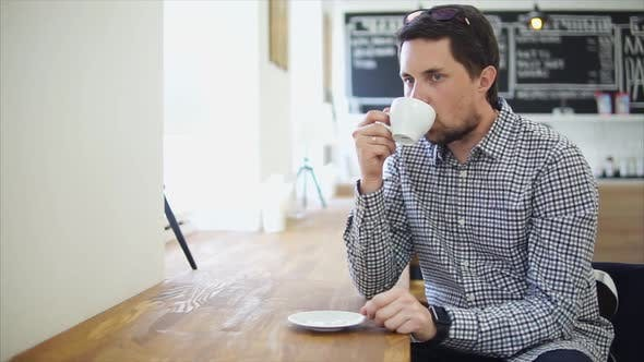 Thumbnail for An Adult Man Enjoys the Taste of the American, Which He Drinks in a Cafe