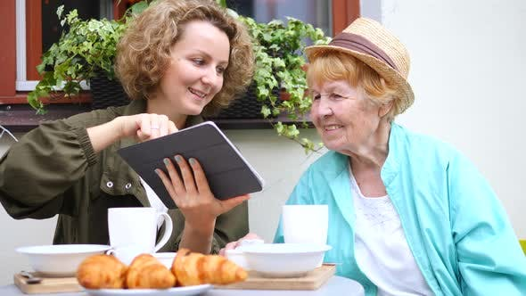 Thumbnail for Granddaughter And Grandmother Using Tablet In Cafe