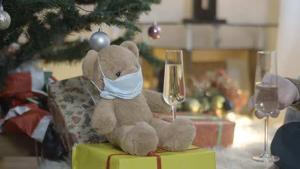 Thumbnail for Teddy Bear in Covid19 Face Mask on Christmas Gift Box with Male Hand Clinking Glass with Champagne
