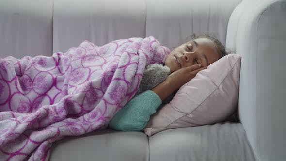 Little Cute Black Girl Sleeping with Toy on Sofa