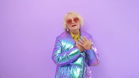 Modern Retired Woman Enjoys a Photo Shoot on Camera in a Studio, Isolated Background