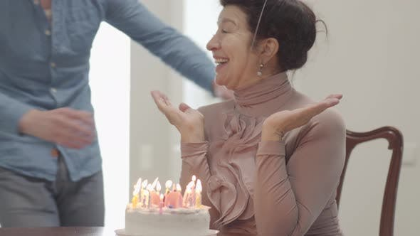 Thumbnail for Portrait Grandma Sitting at the Table in Front of the Small Cake with Many Candles