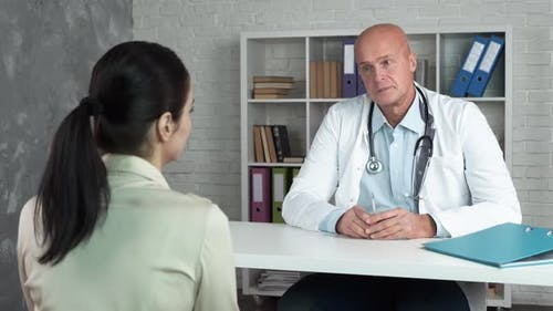 The Doctor Listens To a Young Female Patient During a Consultation. A Physician with a Stethoscope