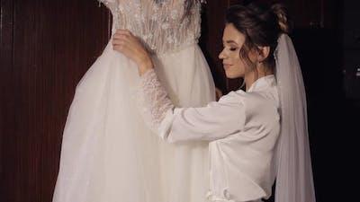 Bride in White Silk Boudoir Dress Touch Her Wedding Dress