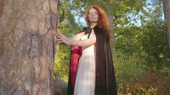 Thumbnail for Beautiful Caucasian Girl with Red Hair in Long White Dress and Black Gown with Red Lining Standing