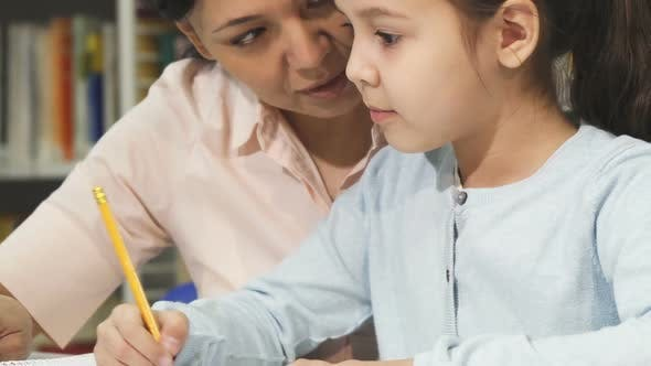 Thumbnail for Cropped Shot of a Cute Little Girl Studying with Her Mother