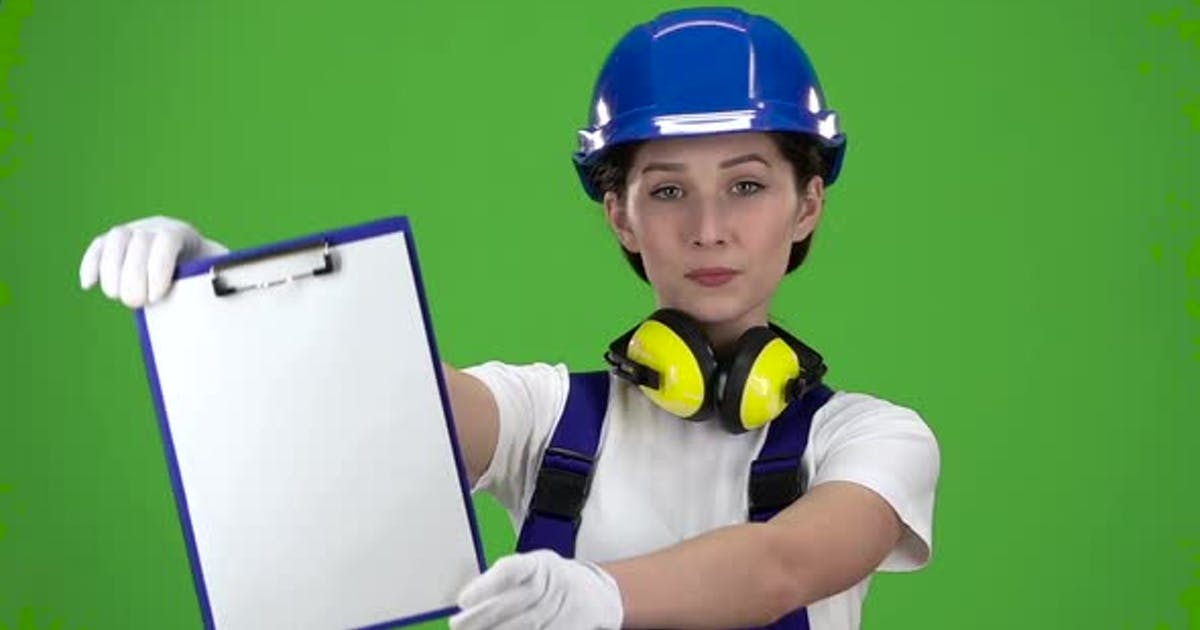 Builder in a Hard Hat and Safety Raises the Paper Plate . Green Screen. Close Up. Slow Motion