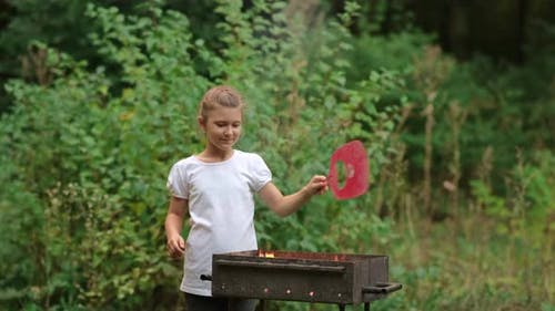 A little girl makes a fire in the grill. Family picnic in the Park.