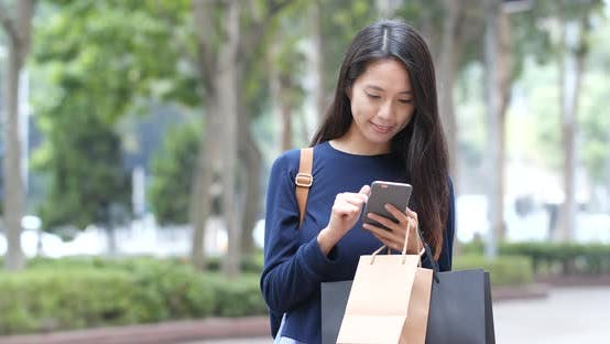 Thumbnail for Shopping woman holding paper bag and use of cellphone