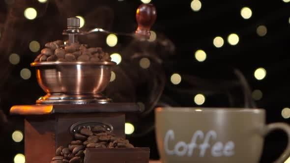 Kaffeemühle und Tasse heißen Kaffee mit einem Rauch