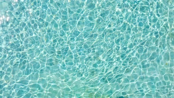 Cover Image for Pool With Blue Water. Water Surface Texture. Top View. Aerial View On Background Of Clean Swimming