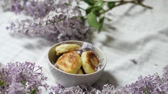 A Bouquet of Lilac Flowers Near a Plate with Cheese Cakes on a White Background