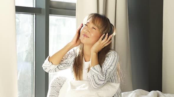 Porträt einer schönen lächelnden Frau in Pyjamas und Musikhören mit Kopfhörern