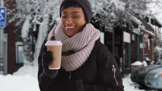 Thumbnail for Smiling young black woman in the snow with warm cup of coffee