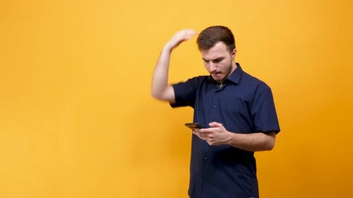 Upset Young Man with a Phone in Hands