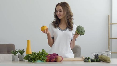 Young Smiling Woman Holding Yellow Tomato and Broccoli Standing at the Table in Modern Kitchen
