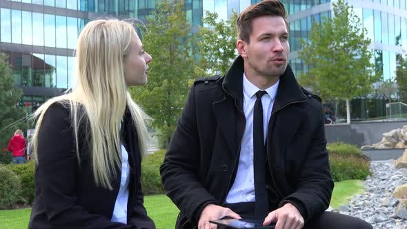 Thumbnail for A Businessman and a Businesswoman Sit on a Bench and Talk in Front of an Office Building