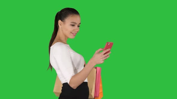 Thumbnail for Young Woman Walking with Shopping Bags Talking on Mobile Phone on a Green Screen