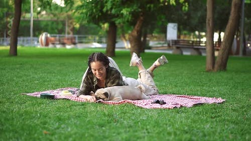 Woman with Dreadlocks Playing with Her Dog on Grass Laying on Plaid Tricking Him with a Little Snack