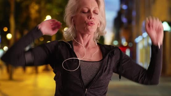 Mature woman jogger going for night run in the city