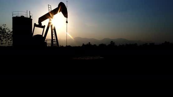 Industrial oil pump jack pumping crude oil for fossil fuel energy with drilling rig in oil field.
