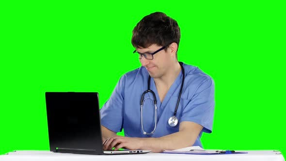 Cover Image for Friendly, Happy Male Doctor in the Office Using Laptop. Green Screen