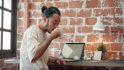 Asian man designer working home using laptop in living room at home.