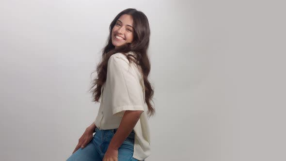 Thumbnail for Young Brunette Woman Alone in Studio Portrait. Smiling Happy Woman