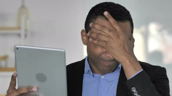 Cover Image for Close Up Of Casual Afro-American Businessman Upset By Loss While Using Tablet