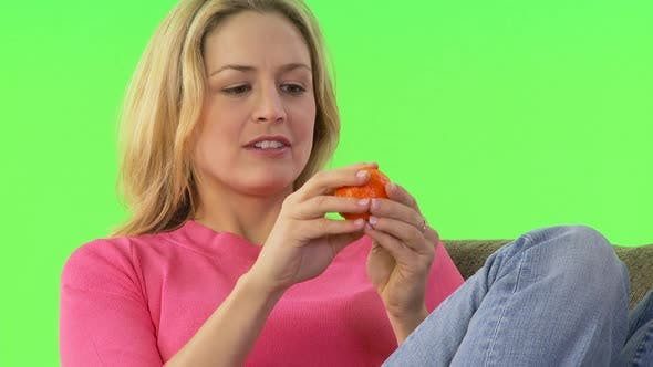 Thumbnail for Woman eating an orange on her couch
