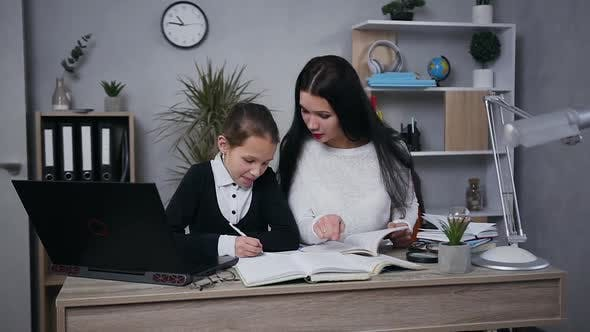 Thumbnail for Teen Girl in School Uniform Doing Her Hometask Together with Pretty Brunette Mother