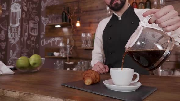 Thumbnail for Barista Man Holds a Pitcher of Fresh Brewed Coffee and Pours in a Empty Cup