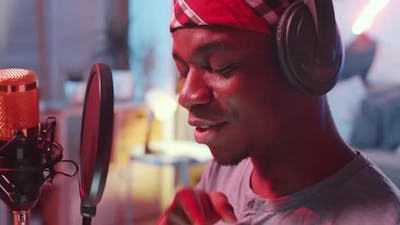 Close Up of Black Man Rapping in front of Microphone in Home Recording Studio