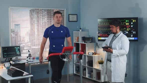 Multiracial Sport Professional Performing Stress Test While the Athlete Walking on Treadmill