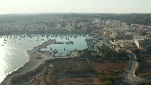 Beach Town with Bay Full of Boats on Malta Island at Sunset, Aerial Drone Perspective
