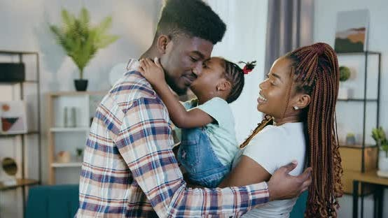 Happy African Parents Kissing and Embracing Daughter